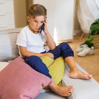 Kleine jongen praten op zijn mobiele telefoon hoge weergave