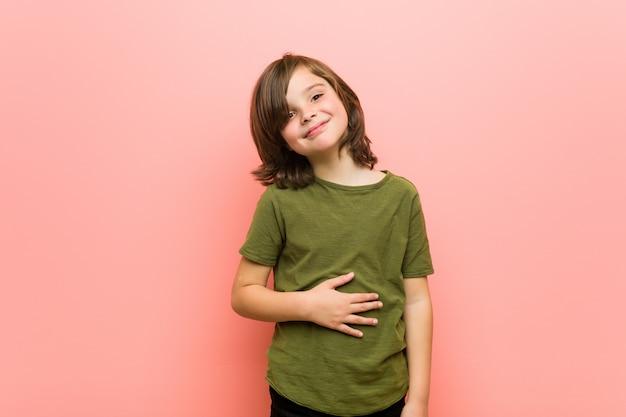 Kleine jongen raakt buik, glimlacht zacht, eten en tevredenheid concept.