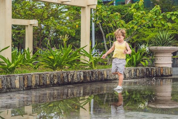Kleine jongen rent door een plas. zomer buiten