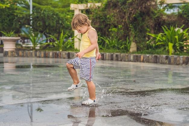 Kleine jongen rent door een plas. zomer buiten.