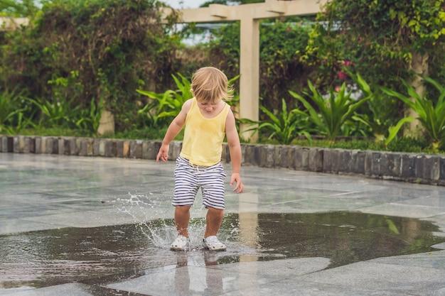 Kleine jongen rent door een plas