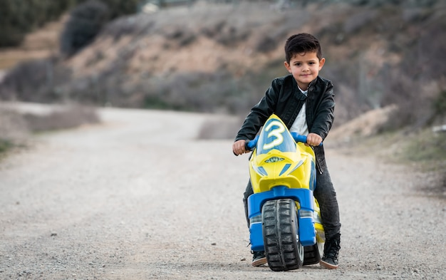 Kleine jongen rijden op motorfiets speelgoed