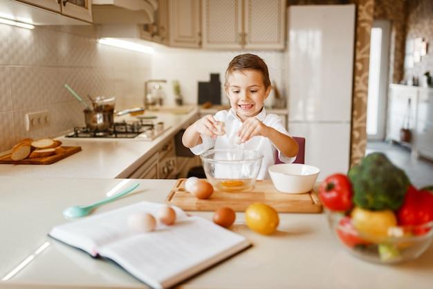 Kleine jongen roert rauwe eieren in een kom