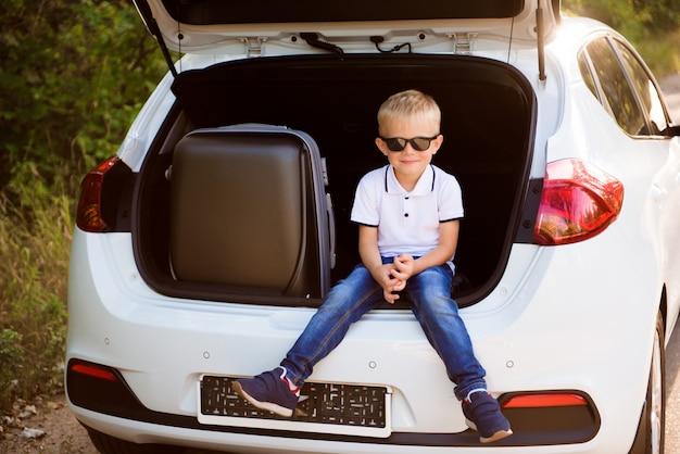 Kleine jongen rust aan de kant van de weg op een road trip. roadtrip met kinderen.