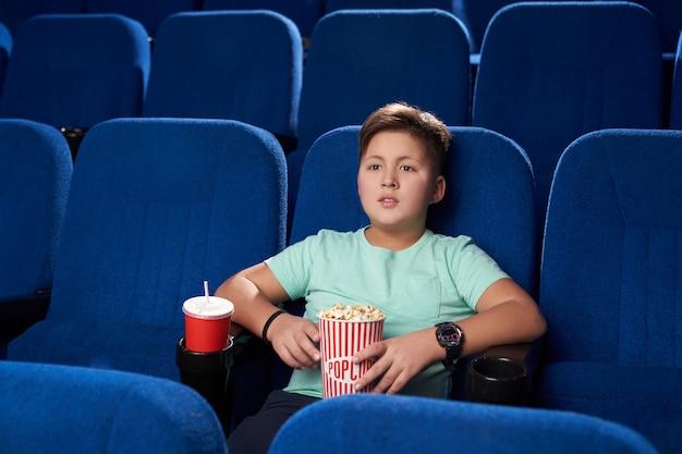 Kleine jongen rust en genieten van actiefilm in de bioscoop