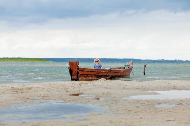 Kleine jongen rust in een boot op het meer