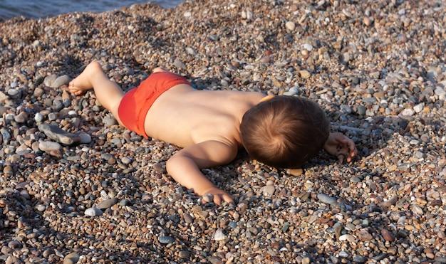 Kleine jongen rust liggend op de stenen op het rotsachtige strand aan de middellandse zee