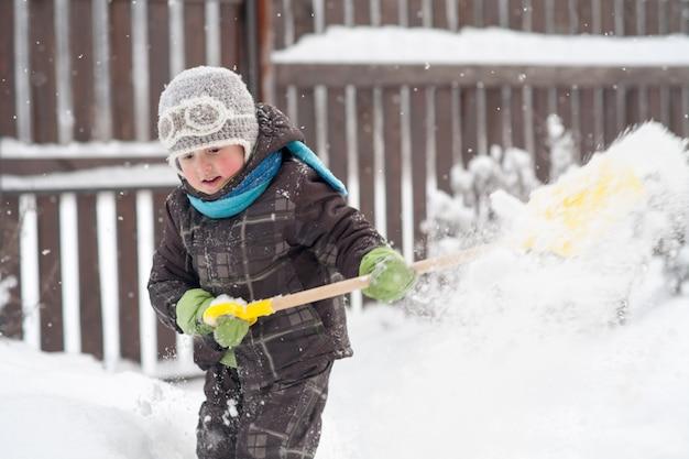 Kleine jongen schept sneeuw weg
