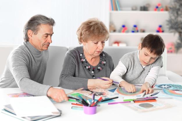 Kleine jongen schilderen met opa en oma. concept van onderwijs