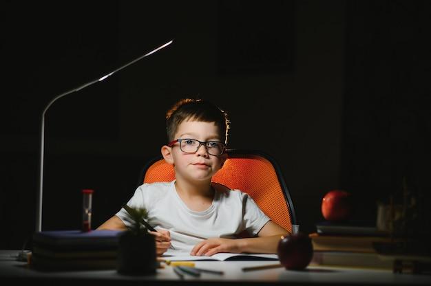 Kleine jongen schildert laat in de avond in een donkere kamer