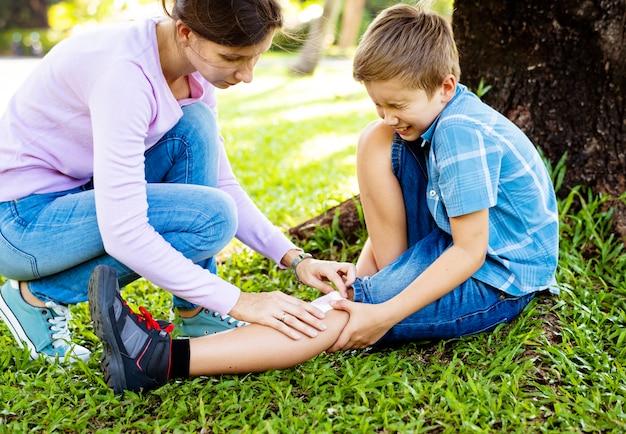Kleine jongen schraapte zijn been tijdens het spelen