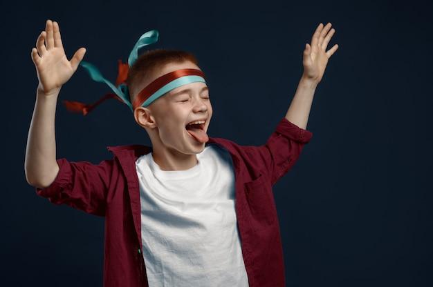 Kleine jongen schreeuwt in studio, winderig effect. kinderen en wind, kind geïsoleerd op een donkere achtergrond, kind emotie