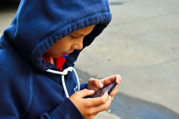 Kleine jongen schrijft sms op de mobiele telefoon.