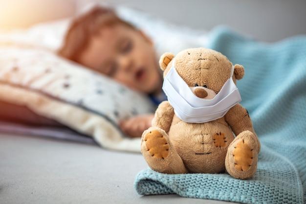 Kleine jongen slaapt in zijn bed met zijn teddybeer die een masker draagt om hem te beschermen tegen het coronavirus covid-19/2019-ncov-concept