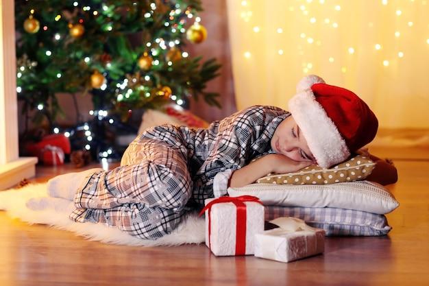 Kleine jongen slapen in de buurt van open haard in de kamer