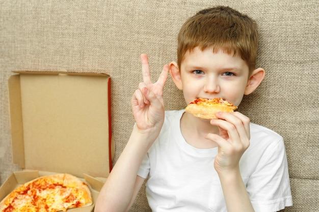 Kleine jongen smakelijke pizza eten op de bank in zijn huis.
