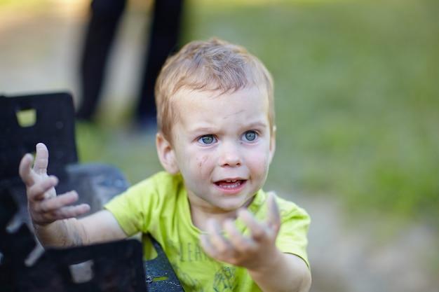 Kleine jongen smeerde zijn handen in de as en was verrast