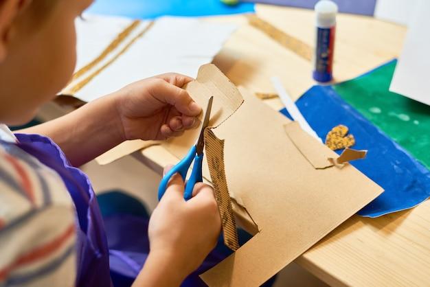 Kleine jongen snijden papier in ambachtelijke klasse