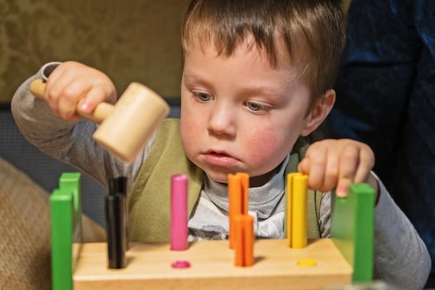 Kleine jongen speelgoed spijkers hameren in een houten bord met hamer