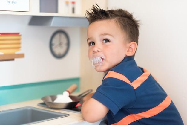 Kleine jongen speelt het spel alsof hij een kok of een bakker in een speelgoedkeuken voor kinderen is.