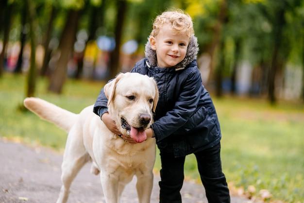 Kleine jongen speelt, loopt met zijn hond labrador in het park in de herfst