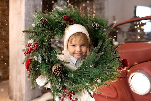 Kleine jongen speelt met de kroon van kerstmis. prettige kerstdagen en fijne feestdagen