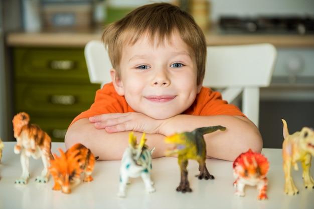 Kleine jongen speelt met dinosaurussen. hagedis-collectie