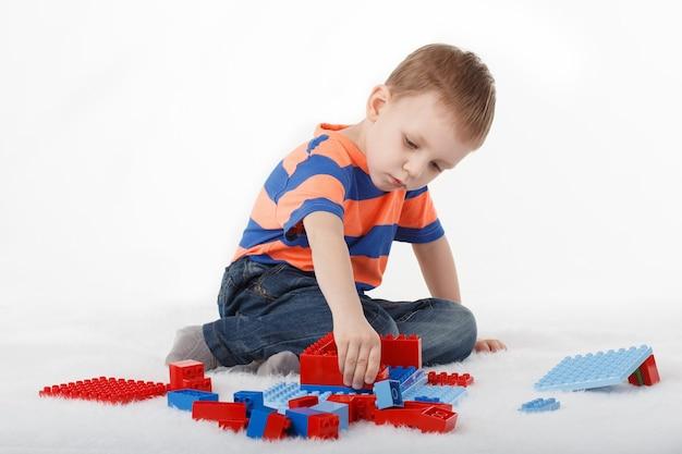Kleine jongen speelt met ontwerper op de vloer op wit
