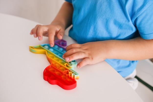 Kleine jongen speelt met regenboog pop it fidget speelgoed. antistress kinderspel. trendy siliconen speelgoed voor kinderen knalt het om stress te verlichten en handmotorische vaardigheden te ontwikkelen. kleurrijk handstuk speelgoed met duwbellen.