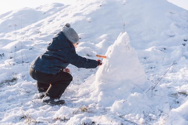Kleine jongen speelt met sneeuw