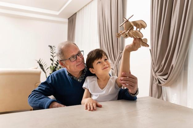 Kleine jongen speelt met zijn grootvader