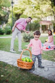 Kleine jongen speelt met zijn ouders in de tuin