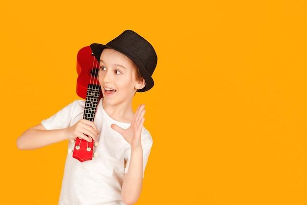 Kleine jongen speelt op hawaiiaanse gitaar of ukelele. gelukkig kind genieten van de muziek. student die ukeleles leert spelen. modieuze jongen in zomer hoed geïsoleerd over oranje achtergrond.