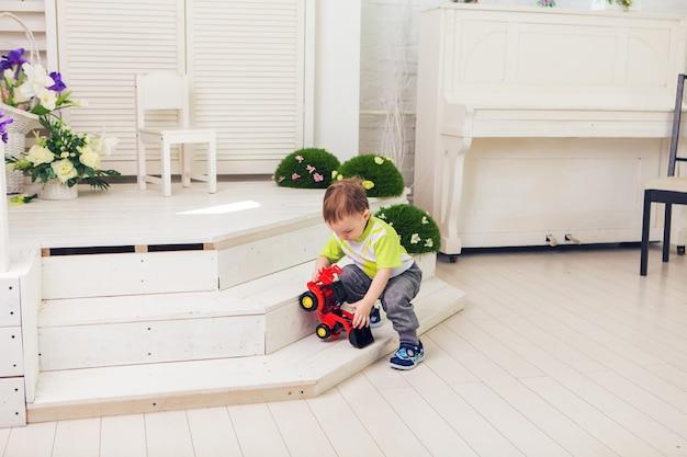 Kleine jongen speelt thuis met speelgoedauto.