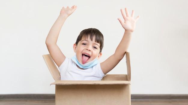 Kleine jongen spelen in cartoon doos