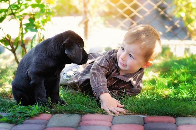 Kleine jongen spelen in de tuin met een puppy labrador