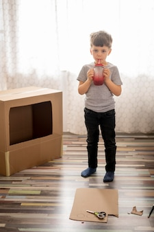 Kleine jongen spelen met cartoon doos