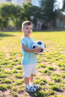 Kleine jongen spelen met een voetbal op het veld in de zomer