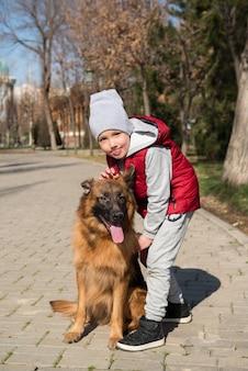 Kleine jongen spelen met hond labrador in lente park
