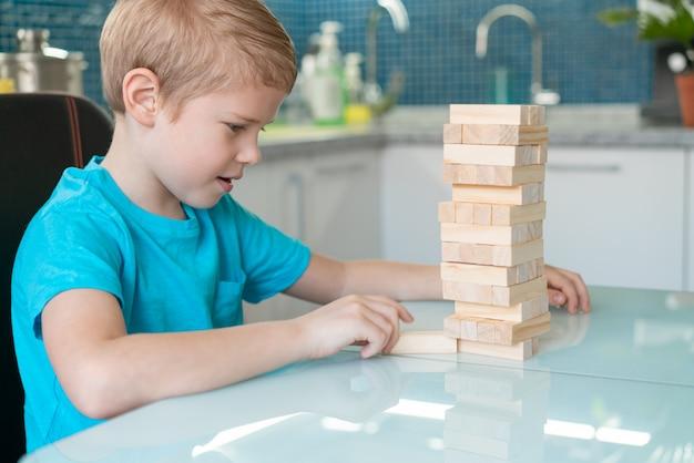 Kleine jongen spelen met houten milieuvriendelijke spel