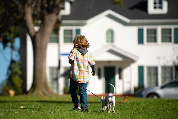 Kleine jongen spelen met puppy gelukkig kind wandelende hond