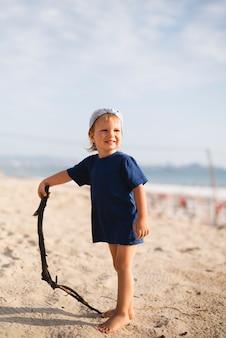 Kleine jongen spelen met stok op strand