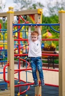 Kleine jongen spelen op de speelplaats.
