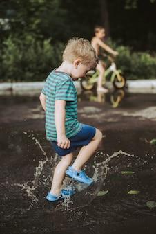 Kleine jongen springen in een plas in de zomer