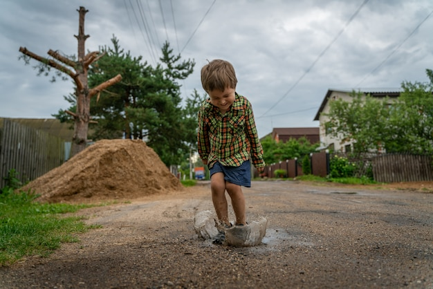 Kleine jongen springt in een plas en spatten vliegen van haar weg