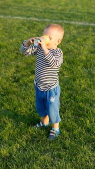 Kleine jongen staande op groen gras met een kopje in beide handen genieten van een verfrissend drankje