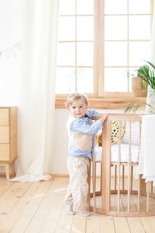 Kleine jongen staat alleen naast een kinderbed in de kinderkamer. de eenzame baby is in kleuterschool dichtbij de wieg. eenzaamheid. milieuvriendelijk kinderkamerdecor in de scandinavische stijl. de jongen is thuis.