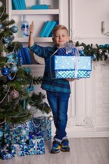 Kleine jongen staat in de buurt van de kerstboom en houdt grote kerstcadeaus.