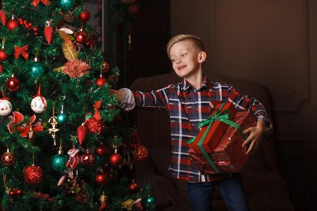 Kleine jongen staat in de buurt van de kerstboom met grote geschenkdozen