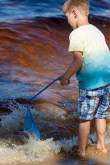 Kleine jongen staat met een visnet direct in de zee.